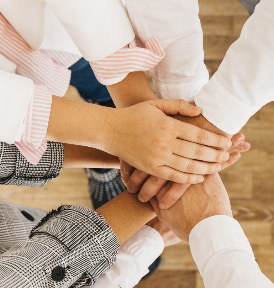 grupo-companeros-trabajo-poniendo-manos-juntas